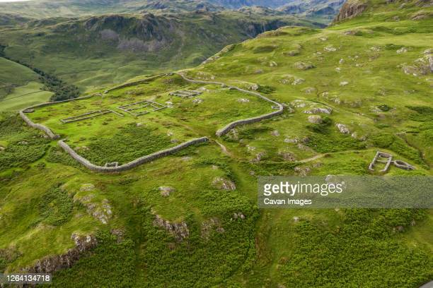 aerial of hardknott roman fort is an archeological site, the remains of the roman fort mediobogdum, located on the western side of the hardknott pass in the english county of cumbria - uk stock pictures, royalty-free photos & images