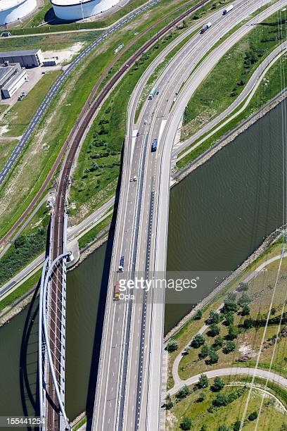 Aerial of highway and railroad crossing a canal