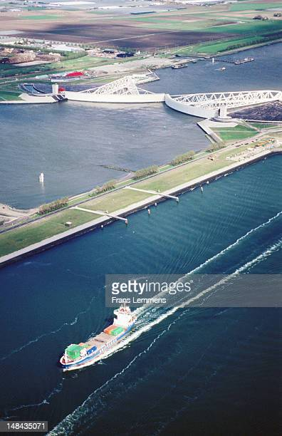 Aerial of Maasvlakte harbour with storm surge barrier and container ship.