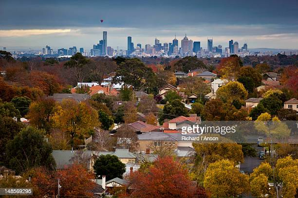 Aerial of Melbourne suburbs in autumn and hot air balloon over city skyline.