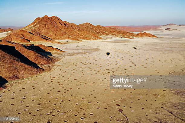Aerial of mountains near Sossusvlei in Namib desert. Circular patches (aka fairy circles) derived from any vegetation & surrounded by tall grass, cause of this phenomenon is unknown. Shadows of two hot-air balloons on grassplain. Namib Naukluft NP, Namibia