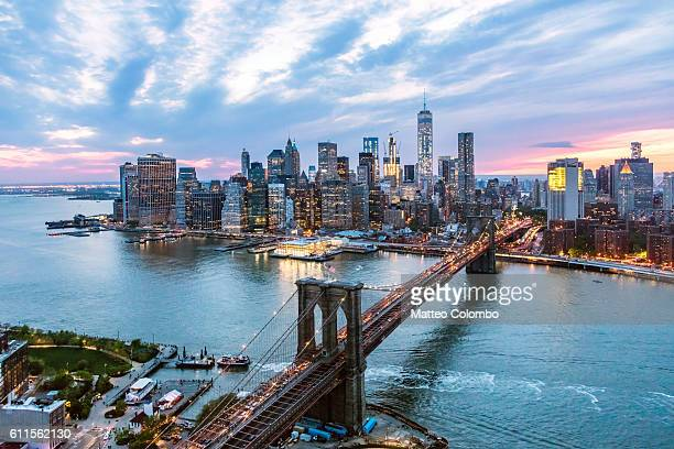 aerial of new york city and brooklyn bridge at dusk - brooklyn bridge stock pictures, royalty-free photos & images