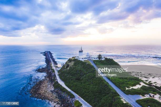 aerial of newcastle and nobby's lighthouse in newcastle harbour, new south wales, australia - 豪州 ニューカッスル ストックフォトと画像