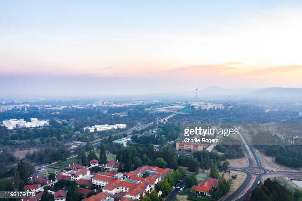 aerial of parliament house and canberra area engulfed in bushfire smog and pollution - australian capital territory stockfoto's en -beelden