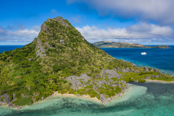 Aerial of Sawa-i-Lau Mountain with cruise ship MV Reef Endeavour (Captain Cook Cruises Fiji) in the distance