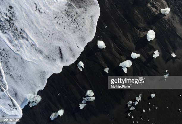 aerial of the icebergs in the black sand beach in jokulsarlon - jokulsarlon lagoon stock photos and pictures