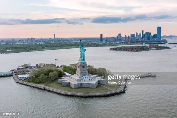 aerial of the statue of liberty at sunset, new york, usa - new york harbour stock pictures, royalty-free photos & images