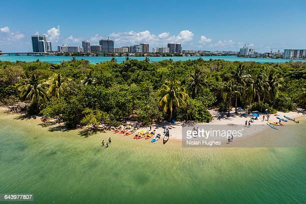 Aerial of tropical beach with people, city in back