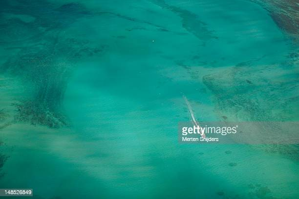 Aerial of turquoise waters with passing speedboat at Kailua Bay.