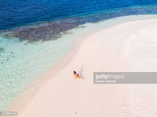 Aerial of woman doing yoga on a beach, Maldives