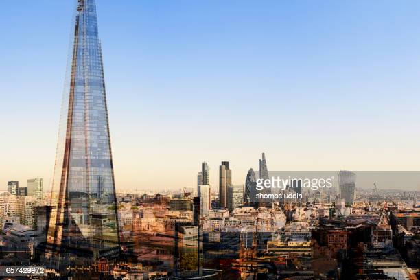 aerial over london city skyline against clear sky - multiple exposure - london financial district stock photos and pictures