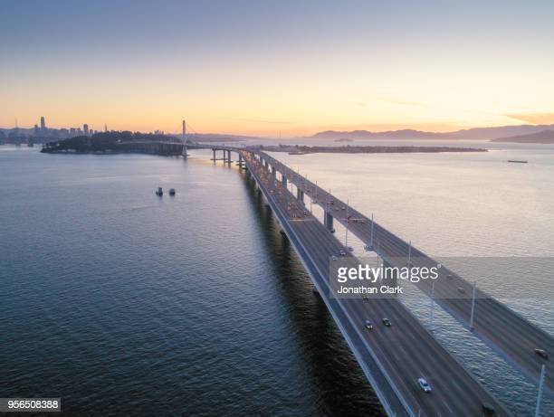 aerial over traffic bay bridge at sunset, san francisco, usa - oakland california skyline stock pictures, royalty-free photos & images