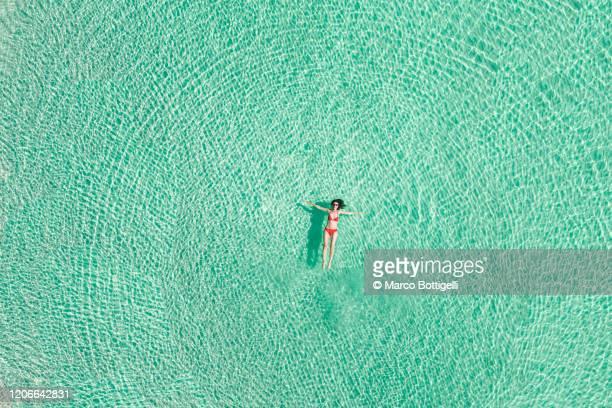 aerial overhead view of woman relaxing on caribbean sea, mexico - flotter sur l'eau photos et images de collection