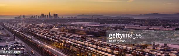 Aerial Panorama of Floodlit Freight Train Yard in Vernon with Downtown LA Skyline at Sunset
