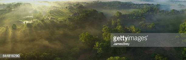 Aerial panorama of foggy valley on edge of town, sunrise