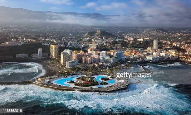 aerial panorama of puerto de la cruz resorts and pools surrounded by sea waves, tenerife, canary islands, spain. - pico de teide stock pictures, royalty-free photos & images