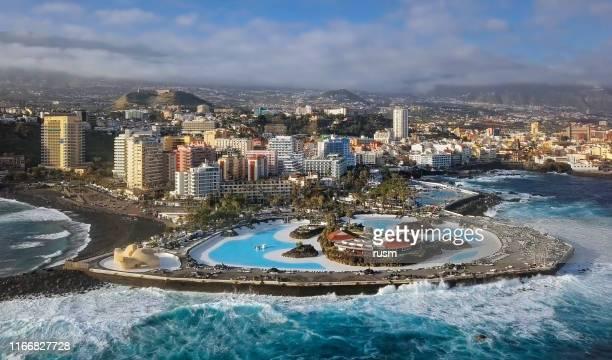 海の波、テネリフェ島、カナリア諸島、スペインに囲まれたプエルト・デ・ラ・クルスのリゾートとプールの空中パノラマ。 - テネリフェ島 ストックフォトと画像