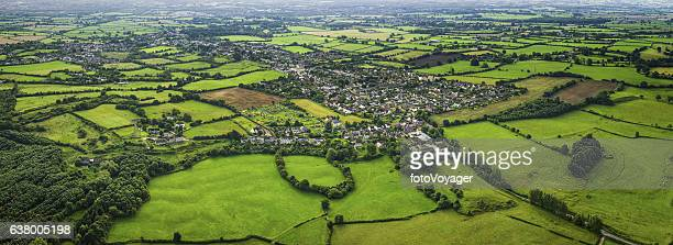 Aerial panorama over country homes surrounded by green patchwork fields
