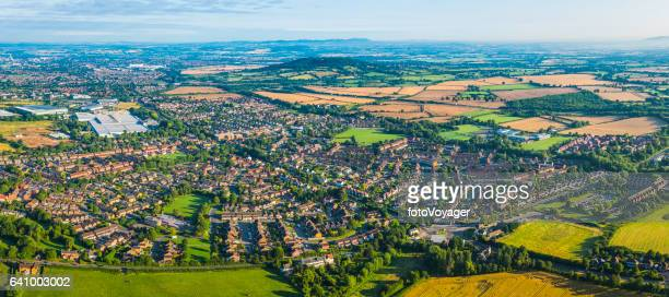 Aerial panorama over country town suburban homes green farmland fields