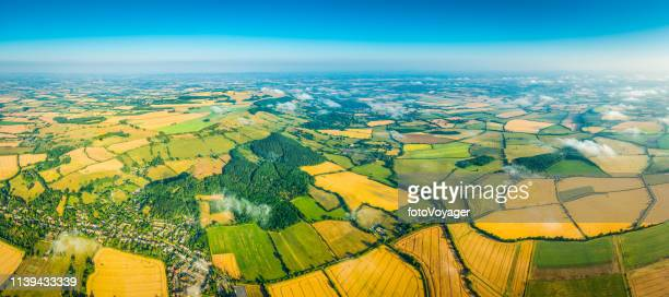 aerial panorama over crop fields farms green pasture summer landscape - organic farm stock photos and pictures