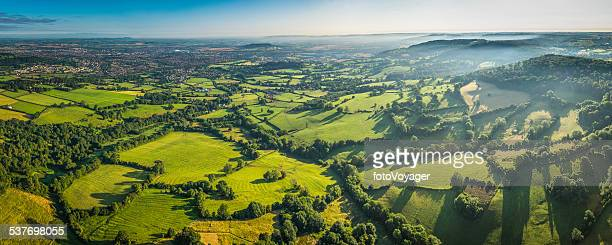 Aerial panorama over green fields misty hills and country town