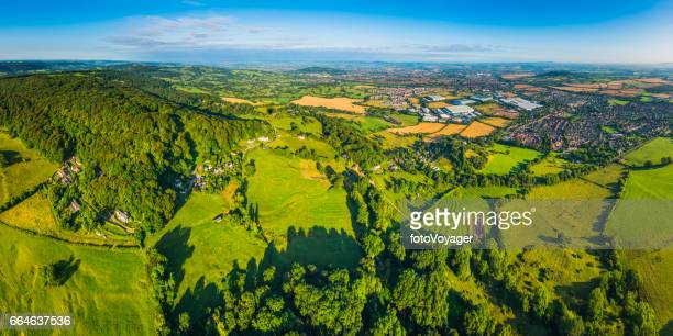 Aerial panorama over green summer countryside farm fields country town