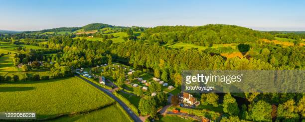 aerial panorama over green summer hills pasture and forests - rolling hills sun stock pictures, royalty-free photos & images
