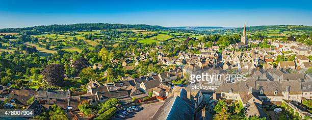 Aerial panorama over idyllic country village cottages green summer fields