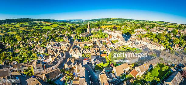Aerial panorama over idyllic country village cottages patchwork summer landscape