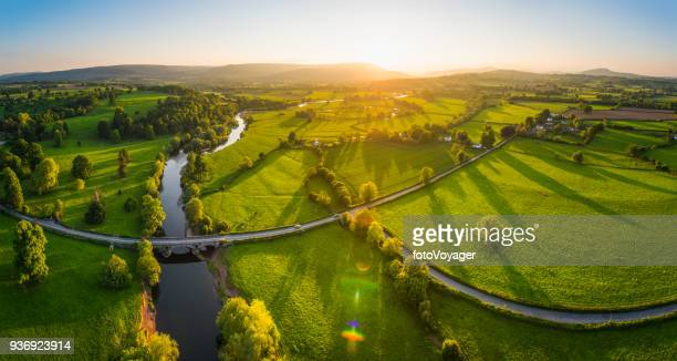 aerial panorama over idyllic countryside green fields mountains golden sunset - river stock pictures, royalty-free photos & images