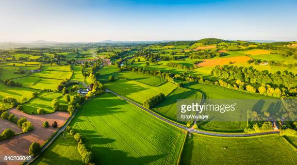 Aerial panorama over idyllic green summer farm fields crops pasture
