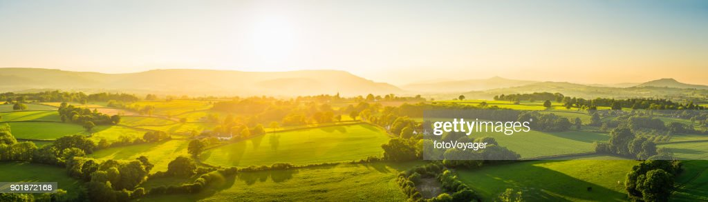 Aerial panorama over idyllic rural landscape golden sunset green pasture : Stock Photo