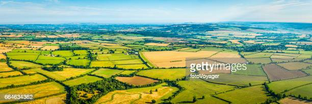 Aerial panorama over patchwork pasture farm fields picturesque rural landscape