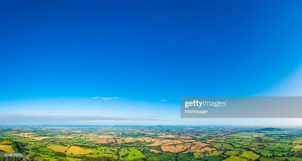 Aerial panorama over picturesque green summer landscape big blue skies : Stock Photo