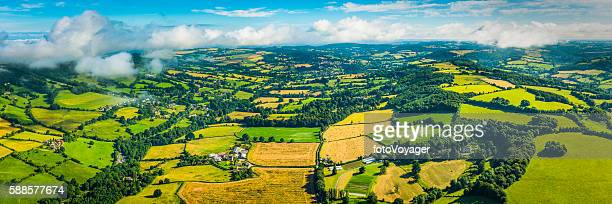 Aerial panorama over picturesque patchwork quilt summer fields farms villages