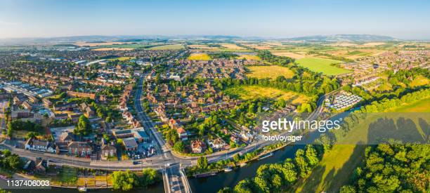 aerial panorama over suburban family homes surround by green fields - district stock pictures, royalty-free photos & images