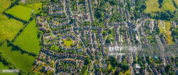 Aerial panorama over suburban homes gardens streets housing green fields