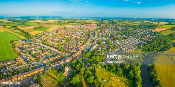 Aerial panorama over town river suburban homes surrounded by fields