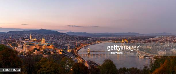 aerial panoramic cityscape of the illuminated budapest in the autumn season with pink sky at dusk - danube river stock pictures, royalty-free photos & images