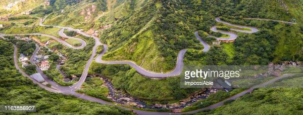 aerial panoramic view from drone of road curve on the green mountain in, jiufen, taiwan - impossiable stock pictures, royalty-free photos & images