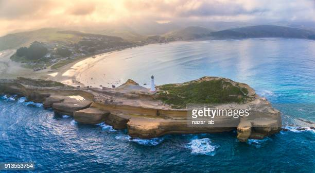 aerial panoramic view of castlepoint lighthouse with castlepoint village in background. - wellington new zealand stock photos and pictures