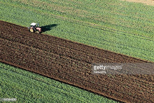 Aerial photo of a tractor plowing a green field