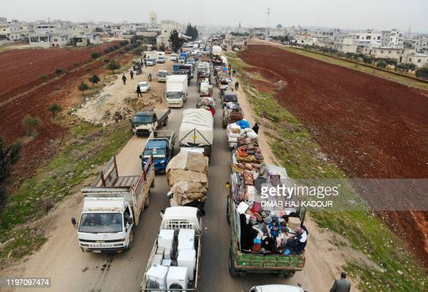 Aerial photo shows displaced Syrians driving through Hazano in the northern countryside of Idlib, after fleeing on January 28, 2020 its southern...