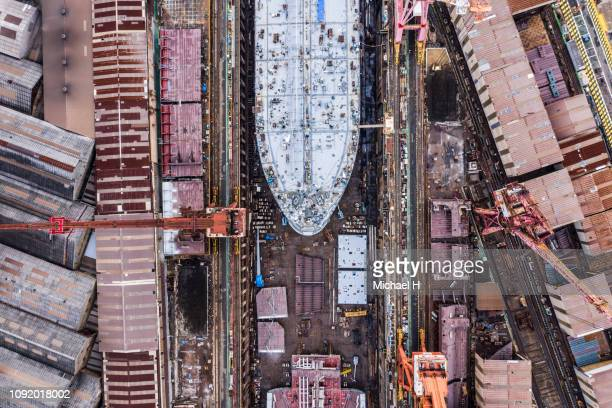 aerial photograph of a large ship under construction at a shipyard. - navy ship stock pictures, royalty-free photos & images