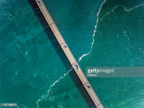 aerial photograph of a river and bridge with cars. - straight stock pictures, royalty-free photos & images