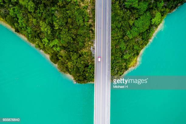 Aerial photograph of crystal clear ocean and bridge.