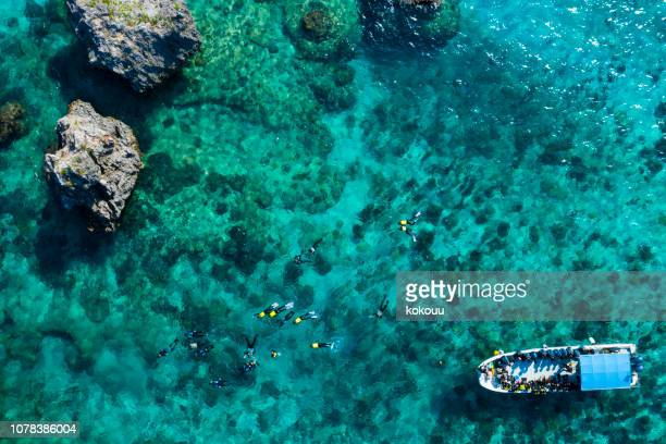 aerial photograph of the beautiful sea and divers. - okinawa prefecture stock pictures, royalty-free photos & images