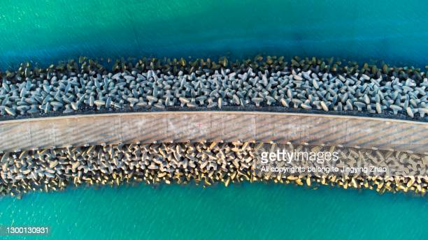 aerial photography of artificial concrete block seawall - seawall stock pictures, royalty-free photos & images