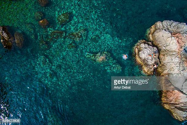 Aerial picture of a group of bloys jumping from the rocks in a paradise beach in the Costa Brava on summertime with beautiful blue waters.
