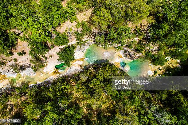 Aerial picture of a kid swimming in a paradise green pools created in a creek in the Catalan Pyrenees during summer.